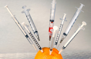 Syringes inserted into an orange